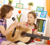 girl playing the guitar while the one is singing
