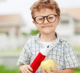 boy holding an apple and a big pencil